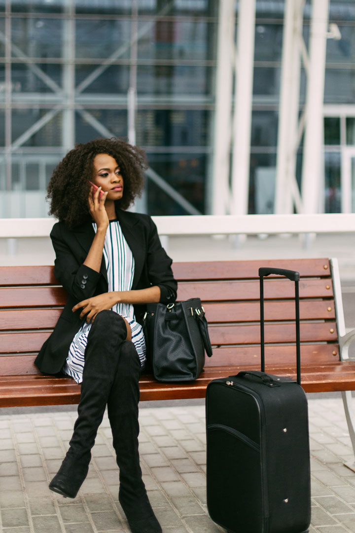 Modern African American businesswoman talking on smart-phone while waiting for the train