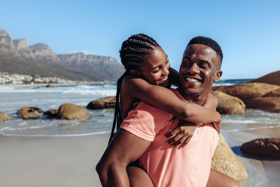 Handsome african man giving piggyback ride to his smiling girlfriend at the beach. Couple enjoying themselves at the seashore.