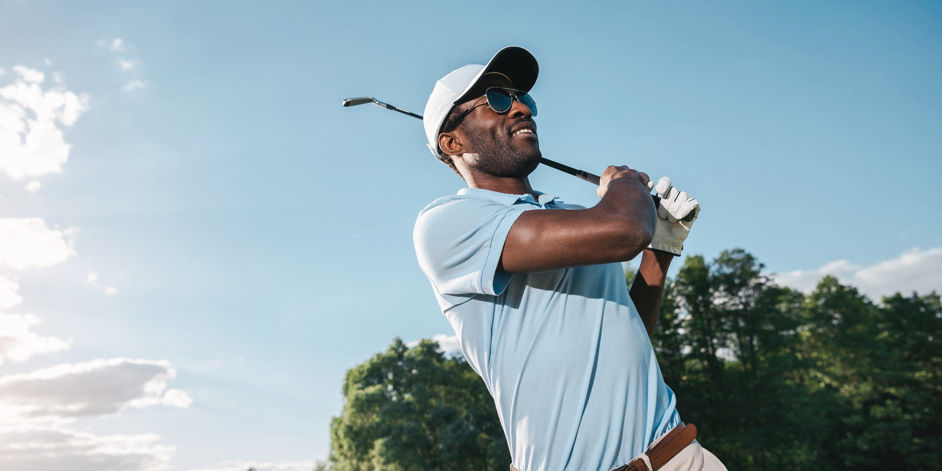 a7ec035b10b Smiling african american man in cap and sunglasses playing golf ...